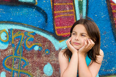 Thinking girl. A little girl with a thoughtful expression against a background of graffiti royalty free stock images