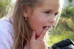 Thinking girl. Thinking little girl with her index finger in front of opened mouth royalty free stock photography