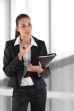 Thinking girl with file. Beautiful businesswoman with file and pen before window Royalty Free Stock Photos
