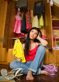 Thinking girl in front of open closet. Can't decide what to wear Royalty Free Stock Image