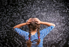 Thinking girl holding head against big blackboard, back view Stock Images