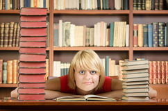 Thinking girl at library table with bunch of books around her. Thinking girl with elbows on library table with bunch of books around her and bookshelf in the stock image