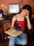 Thinking girl with open book. In front of computer Royalty Free Stock Photo
