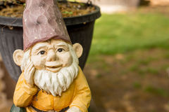 Thinking gnome. A cute little sun worn gnome thinking in the garden with a flower pot behind him royalty free stock photo