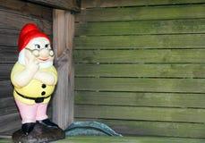 Garden Gnome. Thinking garden gnome in timber garden shelter stock image