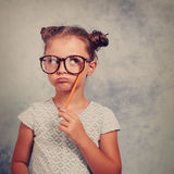 Thinking grimacing kid girl in glasses looking up and have an id Royalty Free Stock Photography