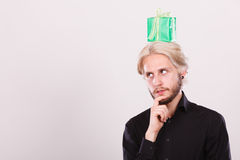 Thinking guy with green gift box on his head Stock Photos