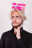 Thinking guy with pink gift box on his head. Celebration and giving concept. Cool young man with pink gift box on his head. Guy thinking looking for present idea Royalty Free Stock Image