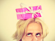 Thinking guy with pink gift box on his head Royalty Free Stock Photography