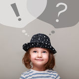 Thinking happy kid girl looking up on question and exclamation signs. On grey background. Creativity business concept on grey background Royalty Free Stock Images