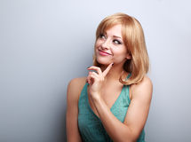 Thinking happy young woman with blond short hair style looking. On empty copy space background stock image