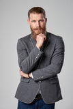 Thinking hipster business man. Confident thinking business man with beard and mustashes in suit standing with folded hands looking out of frame in thoughts over stock images