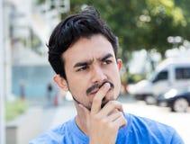 Thinking hispanic guy in the city Stock Photo