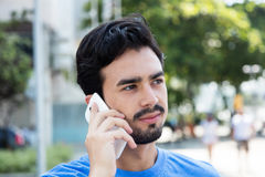 Thinking hispanic guy listening at phone in city. Thinking hispanic guy listening at phone outdoor in the city with buildings in the background Royalty Free Stock Images
