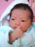 Thinking infant. Lovely Infant on a bed, seems like thinking Royalty Free Stock Images