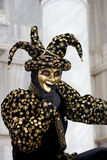 Thinking joker. A joker thinking at the Venice carnival in St. Marc's Square in a gold and black costume Stock Photography