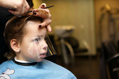 Thinking kid at the barbershop Stock Images