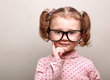 Thinking kid girl in glasses looking happy. On copy space background stock photography