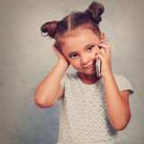 Thinking kid girl talking on mobile phone with happy smile on bl. Ue background with empty copy space. Toned closeup portrait Royalty Free Stock Image