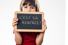 Thinking kid hiding behind writing slate for back to school. Thinking little kid hiding behind a French writing slate to warn about a scary back to school on Royalty Free Stock Images