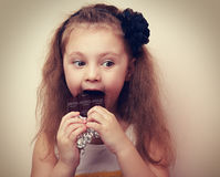 Thinking kid with humor look eating chocolate. Vintage. Closeup portrait Stock Images