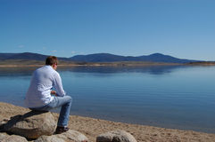 Thinking on the Lake Shore. Rear view of a man sitting on a lake shore Royalty Free Stock Photo