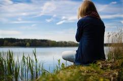 Thinking at a lake. Women meditationing at a lake royalty free stock image
