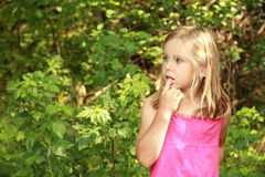 Thinking little girl. Little girl in ping thinking in a forest stock photos
