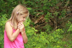 Thinking little girl. Little girl in ping thinking in a forest royalty free stock photography