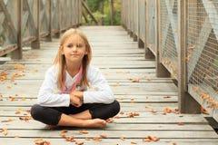 Thinking little girl on bridge stock photo