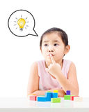 Thinking little girl with idea bulb above the head. And wooden building blocks on table isolated on white background Stock Photos