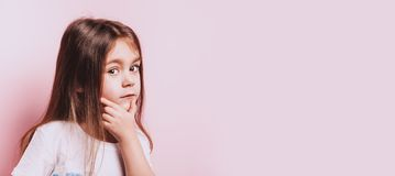 Thinking little girl on pink background. Emotional child portrait. Copyspace for text stock photography