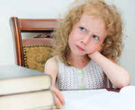 Thinking little girl. Reading a book royalty free stock photo