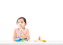 Thinking little girl with wooden building blocks on table. Isolated on white background stock images