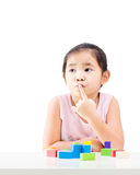 Thinking little girl with wooden building blocks on table Royalty Free Stock Images