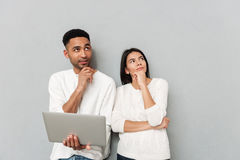 Thinking loving couple standing over grey wall using laptop Stock Photo