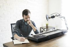 Thinking about lyrics of his new song. Hispanic male songwriter thinking while writing new song in his book stock photo