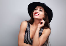 Thinking makeup woman in fashion hat looking up and dreaming abo Stock Image