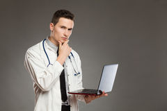 Thinking male doctor with a laptop Stock Photos