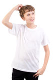 Thinking male teen scratches head. Wearing a white t-short isolated on white background Stock Photo