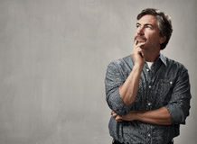 Thinking man. Thinking caucasian man portrait over gray wall background stock image