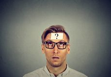 Thinking man in glasses with question mark looking up stock photography