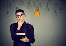 Thinking man looking up with light idea bulb above head Royalty Free Stock Image