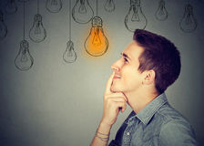 Thinking man looking up with light idea bulb above head. Isolated on gray wall background Stock Photography
