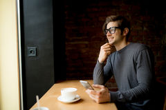 Thinking man looking in the window while drinking coffee in morning in coffee while using phone royalty free stock photography
