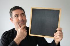 Thinking man looks at an empty blackboard Stock Photo