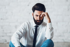 Thinking man making decision. Young handsome bearded man solving the business problem. Perfect skin and hairstyle of Royalty Free Stock Photos