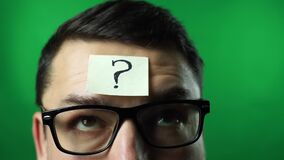 Thinking man with question mark on gray wall background green screen background.  stock footage