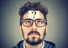 Thinking man with question mark looking up stock photos