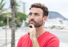 Thinking man with red shirt and beard in the city Stock Photos